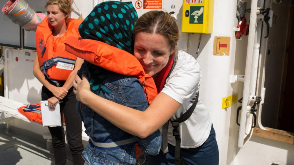 Catherine Flanigan hugs a survivor as they prepare to disembark the Aquarius