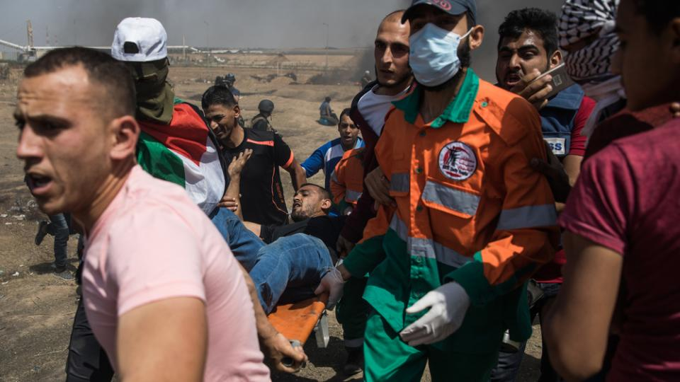 A palestinian protestor shot by a sniper is rushed to help on a stretcher