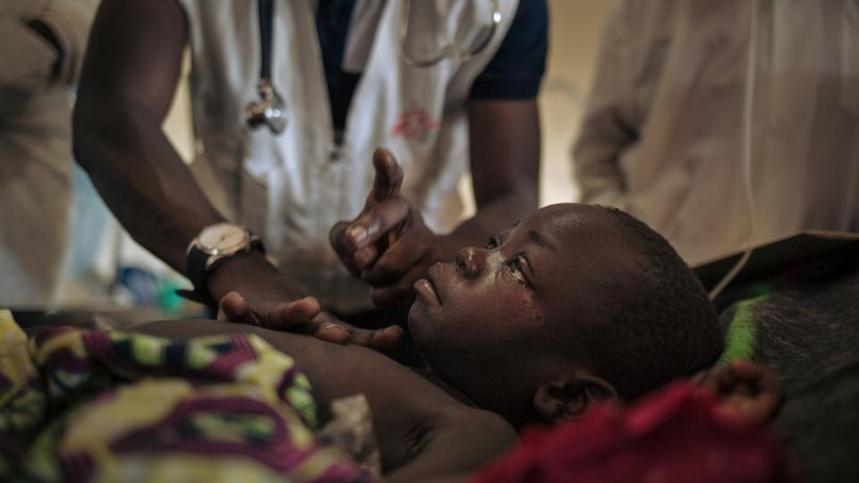 A young girl with measles is examined in the MSF measles unit at Biringi Hospital, Ituri Province, northeastern DRC