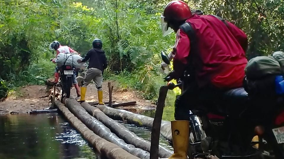 An MSF mobile medical team cross a makeshift bridge in DRC