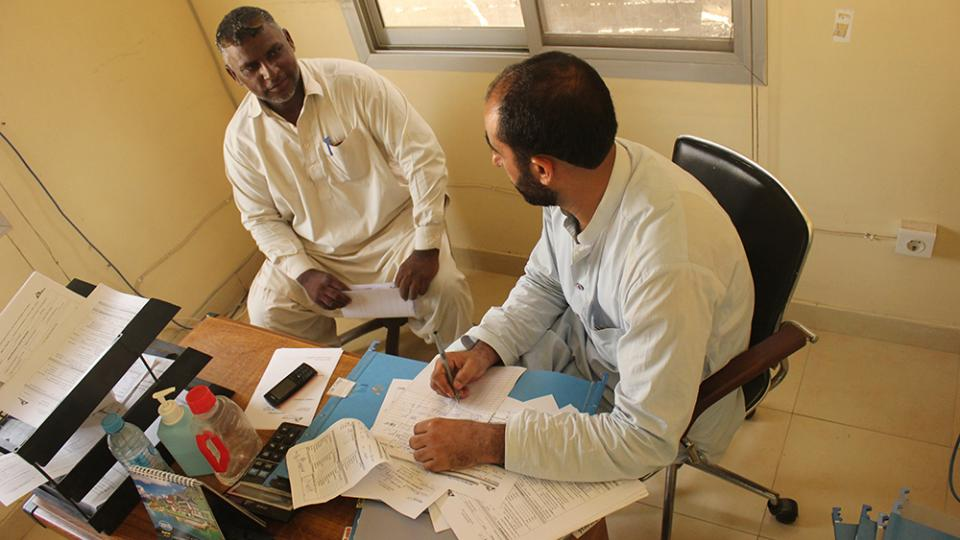 Khurshid Ahmad consulting with a patient in Pakistan