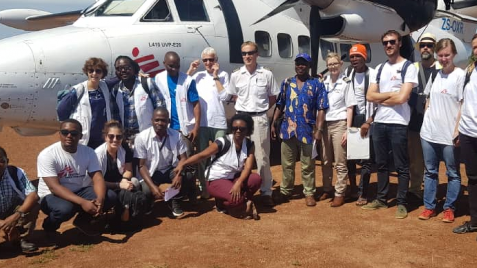 The MSF team poses by a small plane