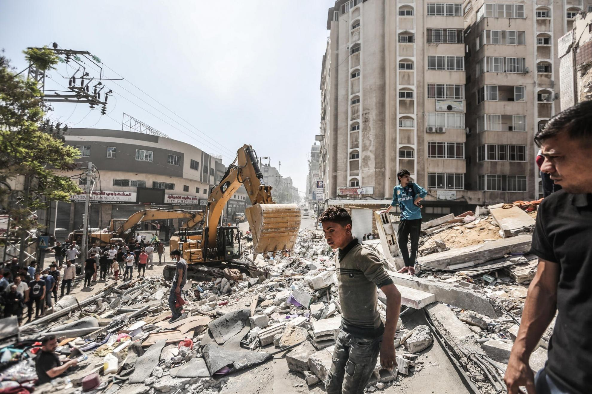 People clearing debris after an Israeli airstrike destroyed a residential tower in Gaza City