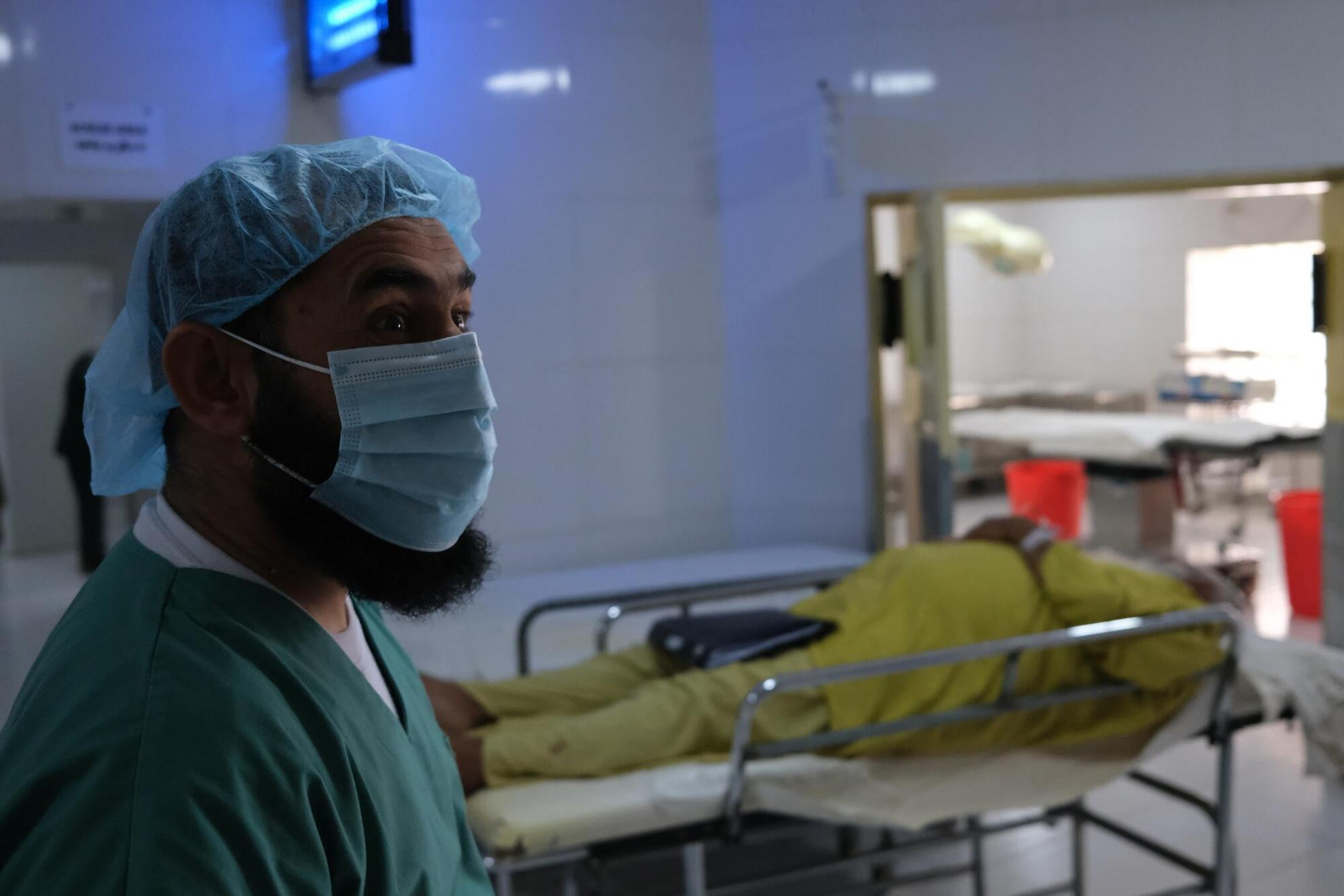 An MSF surgeon prepares for surgery to remove a kidney stone from a 63-year-old man in the operating theatre of Boost hospital, May 2021