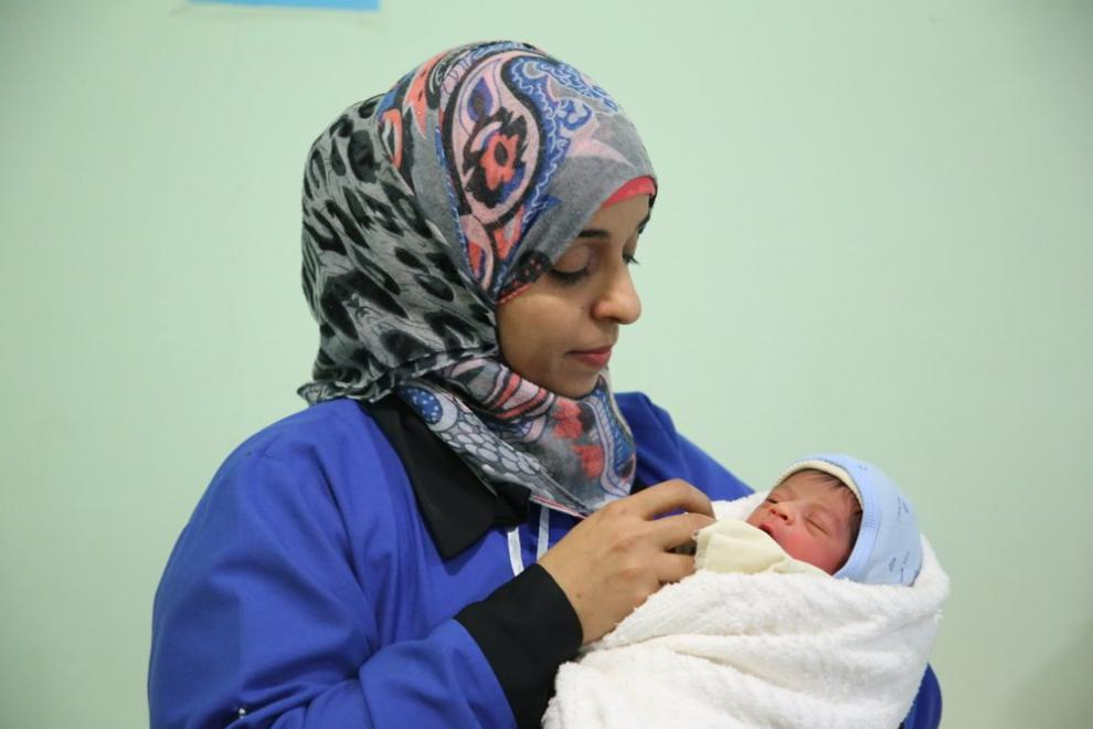 An MSF midwife holding a newborn at a mother and child hospital in Yemen