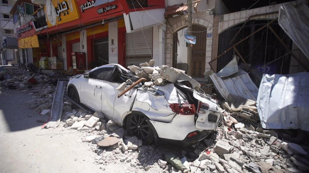 A car in Gaza, crushed under the fallen parts of a damaged building