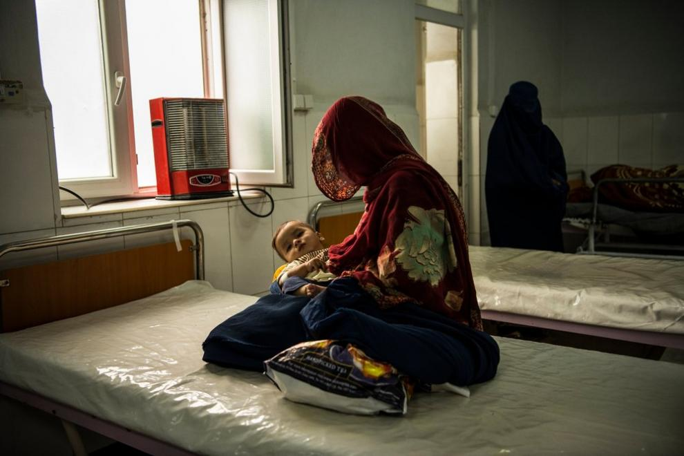 Imran, suffering from a chest infection, is held by his mother in the female observation ward at Boost hospital, October 2020