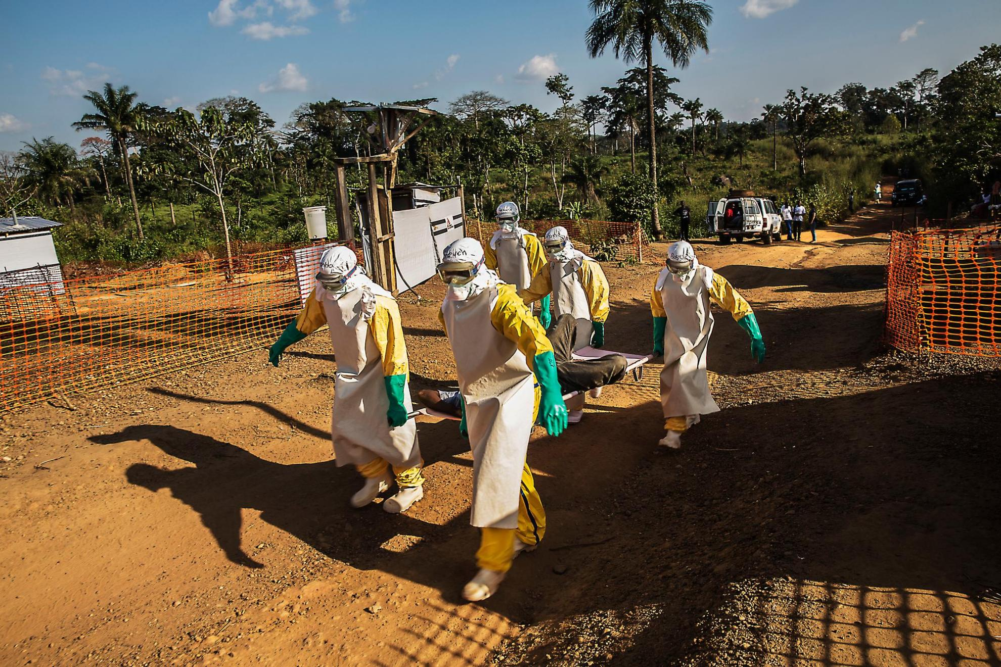 December 2014: A team of MSF healthcare workers carry an Ebola patient in Sierra Leone
