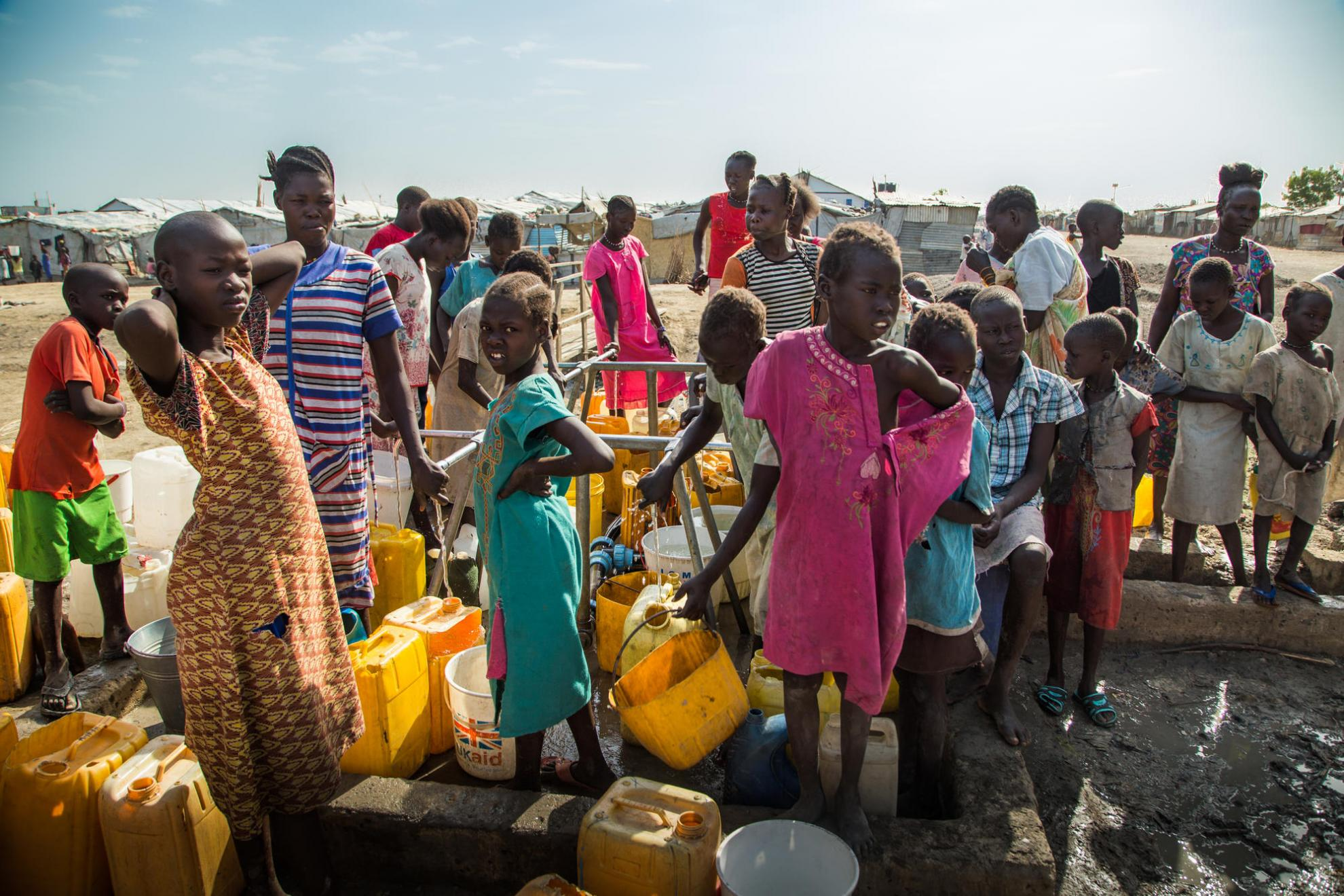Crowded conditions as women and children queue for water in a PoC camp