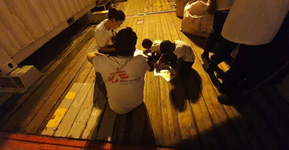 MSF staff on board the Ocean Viking sit with two rescued children