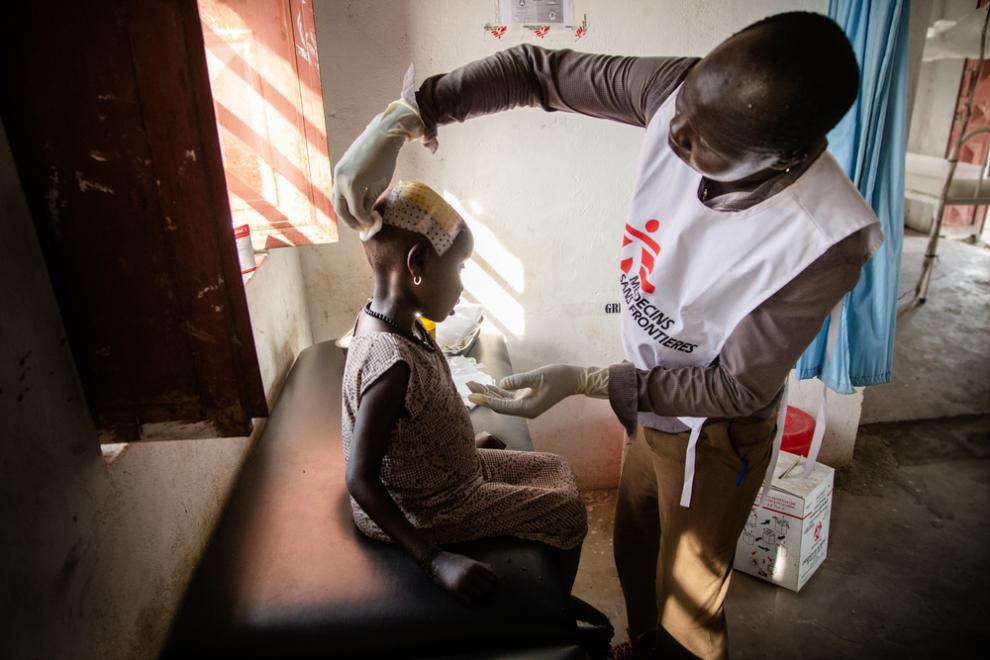 An MSF staff member examines a young patient with a head injury at a hospital in Ulang, South Sudan