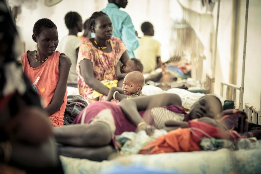 A baby sits with their mother in the MSF hospital at Bentiu camp
