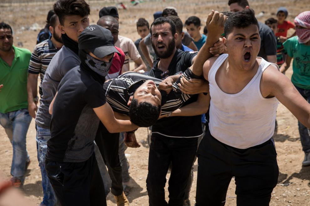 A Palestinian protester shot by an Israeli sniper is carried to safety during protests in May 2018