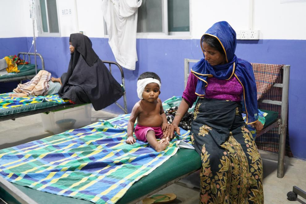 A mother sits with her child, who is recovering from burn injuries, at MSF's hospital in Kutupalong