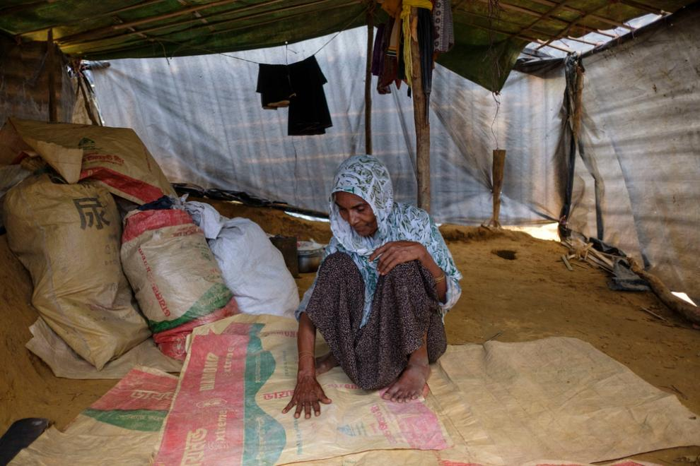 A Rohingya refugee woman sits in her makeshift shelter