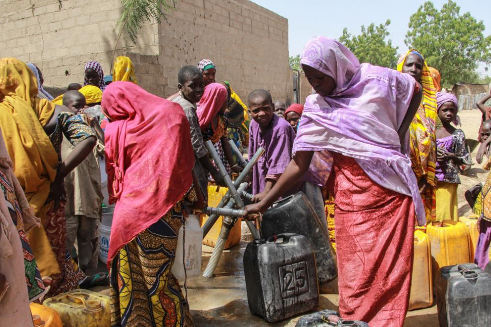 Brightly dressed women fill their jerry cans at a water point