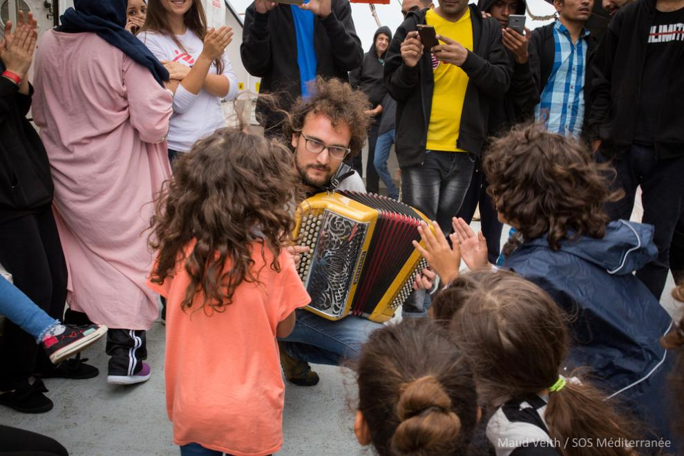 Aloys plays the accordion while the Aquarius waits in international waters off Malta for transfer instructions