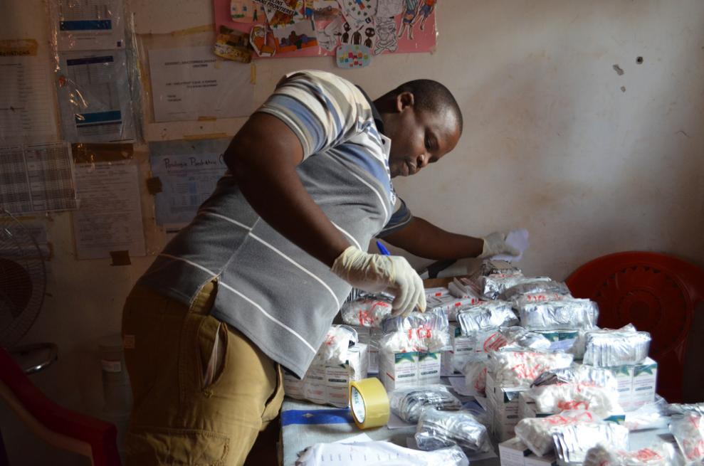 A pharmacist in Zémio prepares ninety days' worth of HIV medications for 26 people in a community group