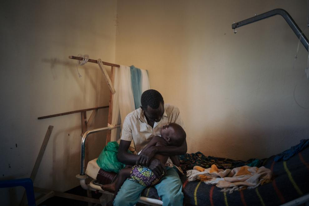 Joseph Drobho Giria holds his two-year-old daughter, Bhileru Drobho, who suffers from measles, in the measles unit run by MSF at Biringi Hospital, Ituri Province, northeastern Democratic Republic of Congo, on 06 November 2019