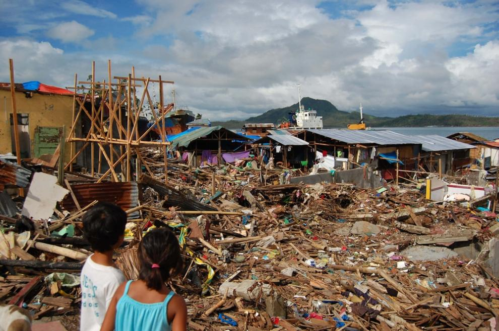 Two children look out across the Tacloban slum, which was badly damaged by typhoon Haiyan, Feb 2014.