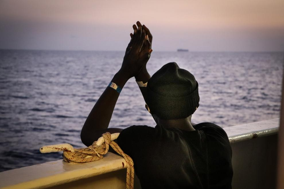 A person who has been rescued by the Sea Watch 4 looks out over the Mediterranean Sea