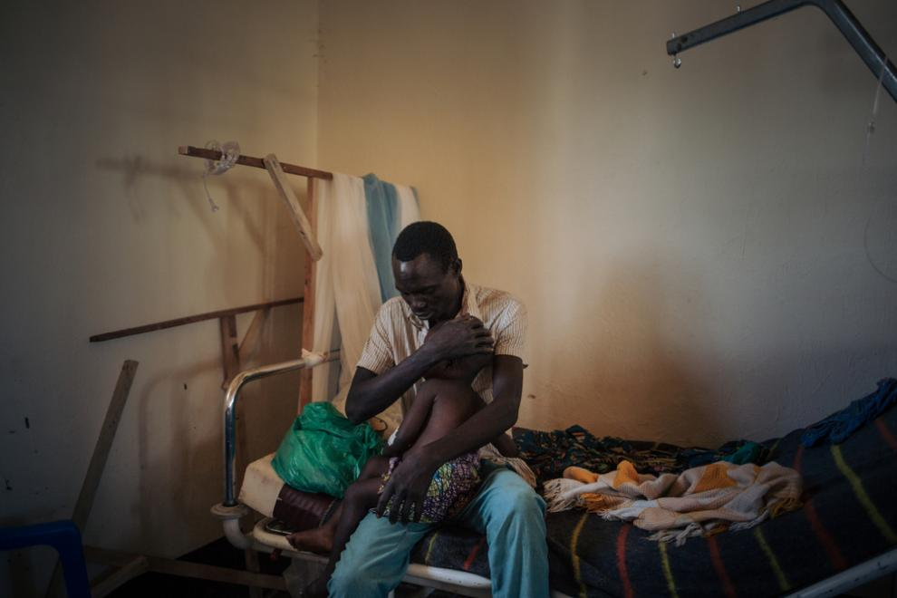 Joseph Drobho Giria holds his two-year-old daughter, Bhileru Drobho, in the measles unit run by MSF at Biringi Hospital in Ituri Province, northeastern DRC