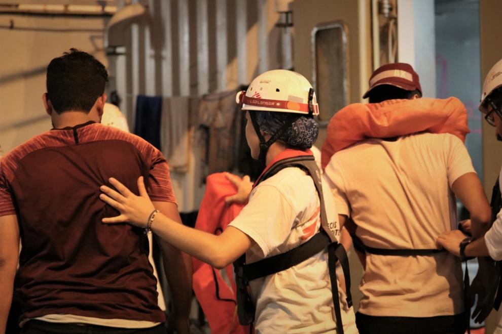 MSF staff help people as they come on board the deck of the rescue ship, the Ocean Viking. Minutes before, they had been rescued from a wooden boat in distress on the Mediterranean. Sept 2019.