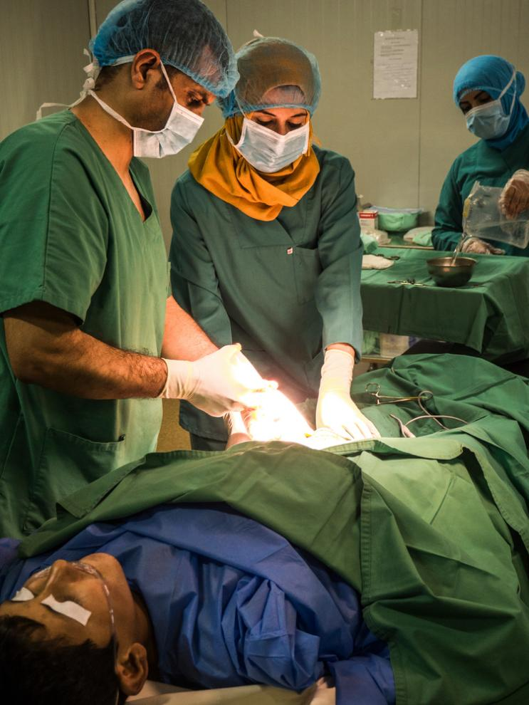 Surgeons operate on a patient in Al Qayyarah