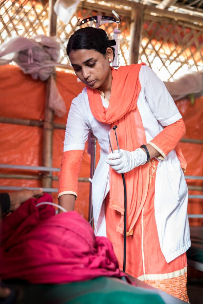 MSF Nurse Masuma Akter measuring the blood pressure of a patient in the Kutupalong Clinic