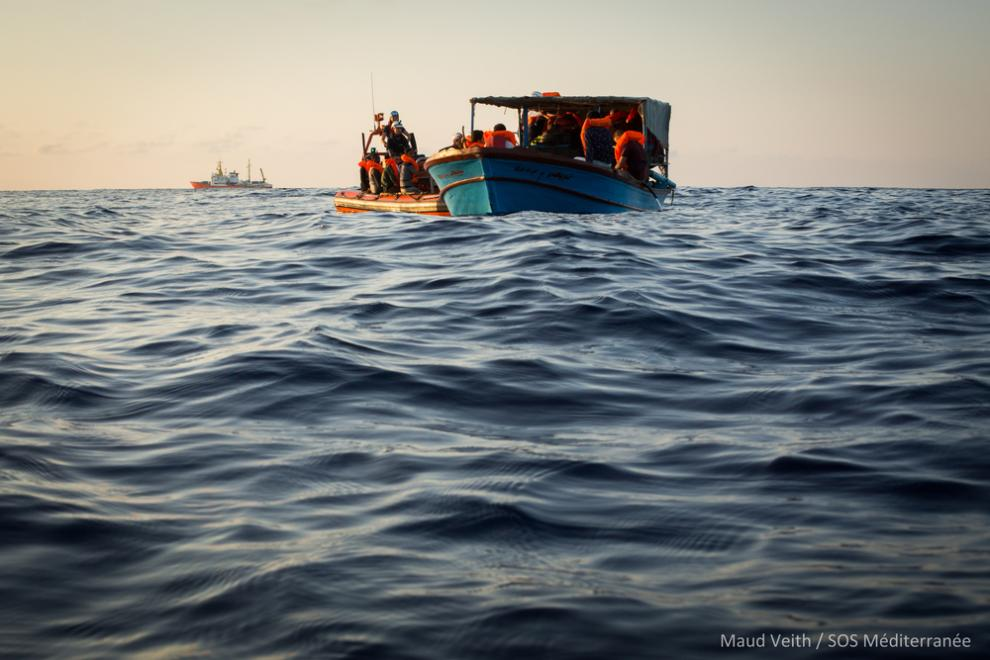 People are transferred from the wooden boat to the Aquarius' rigid hulled inflatable boats