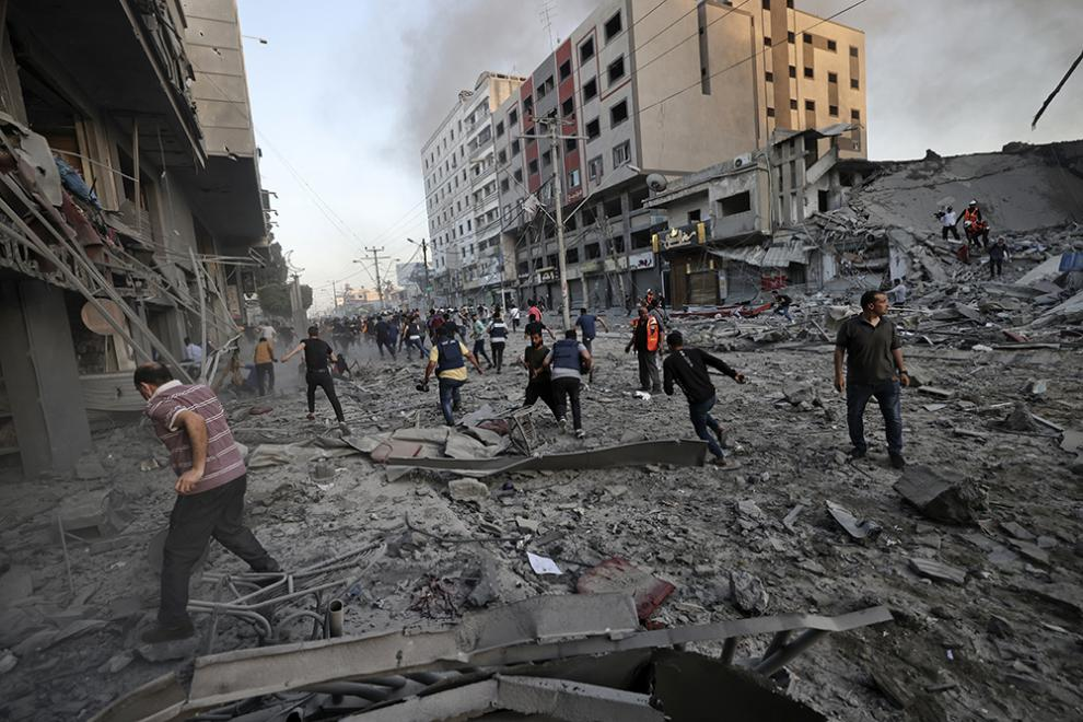 People amidst the rubble in front of Al-Sharouk tower that collapses after being hit by an Israeli air strike, in Gaza City, on May 12, 2021