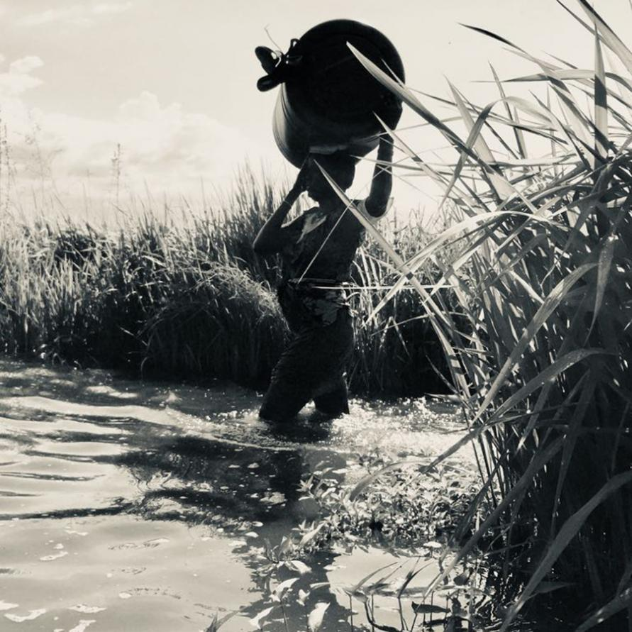 A woman carrys MSF supplies through the swamp