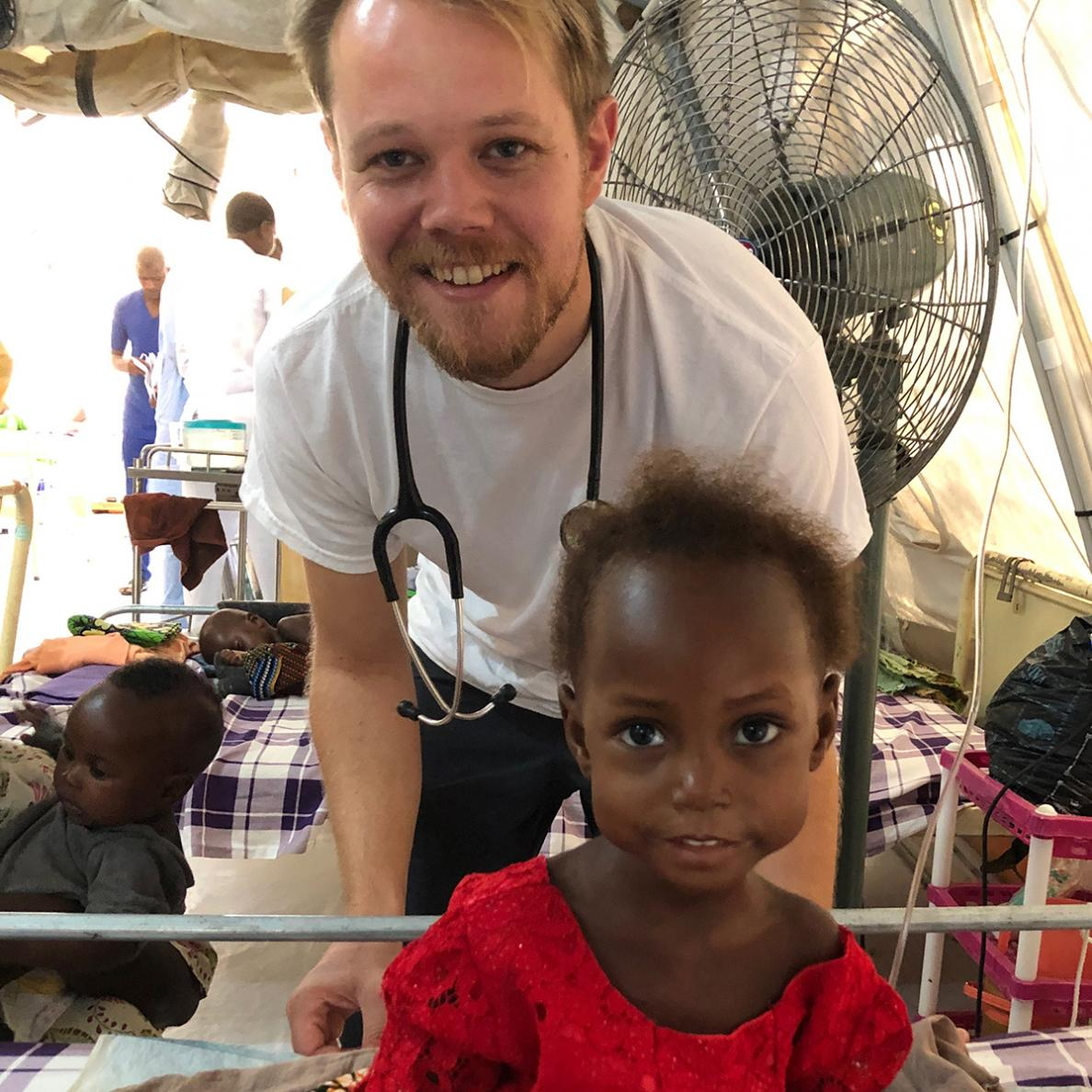Hauwa, a young malnutrition patient, sits up on a hospital bed, alongside MSF paediatrician Alexandre