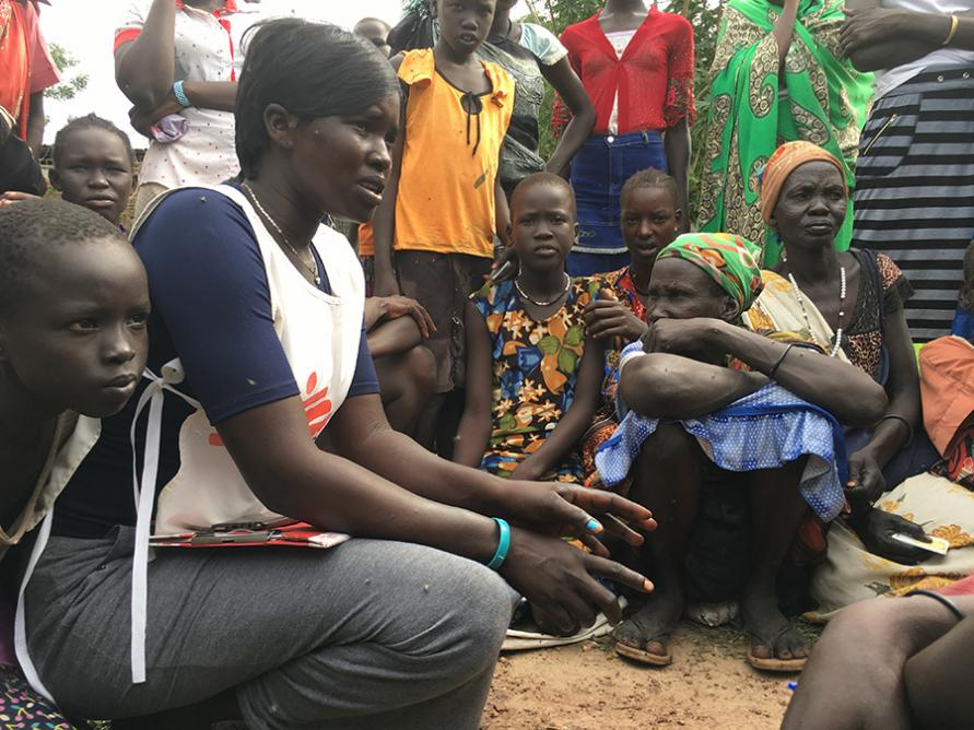 An MSF community health worker talking with local people