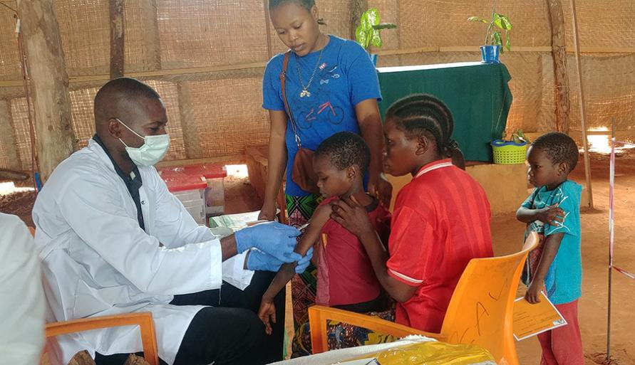 An MSF medic wearing a face mask and gloves while vaccinating a child