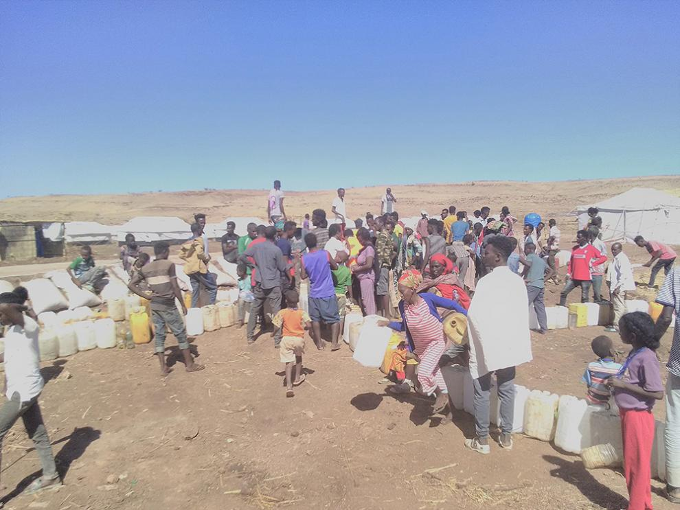 People surrounded by jerry cans at a water collection point