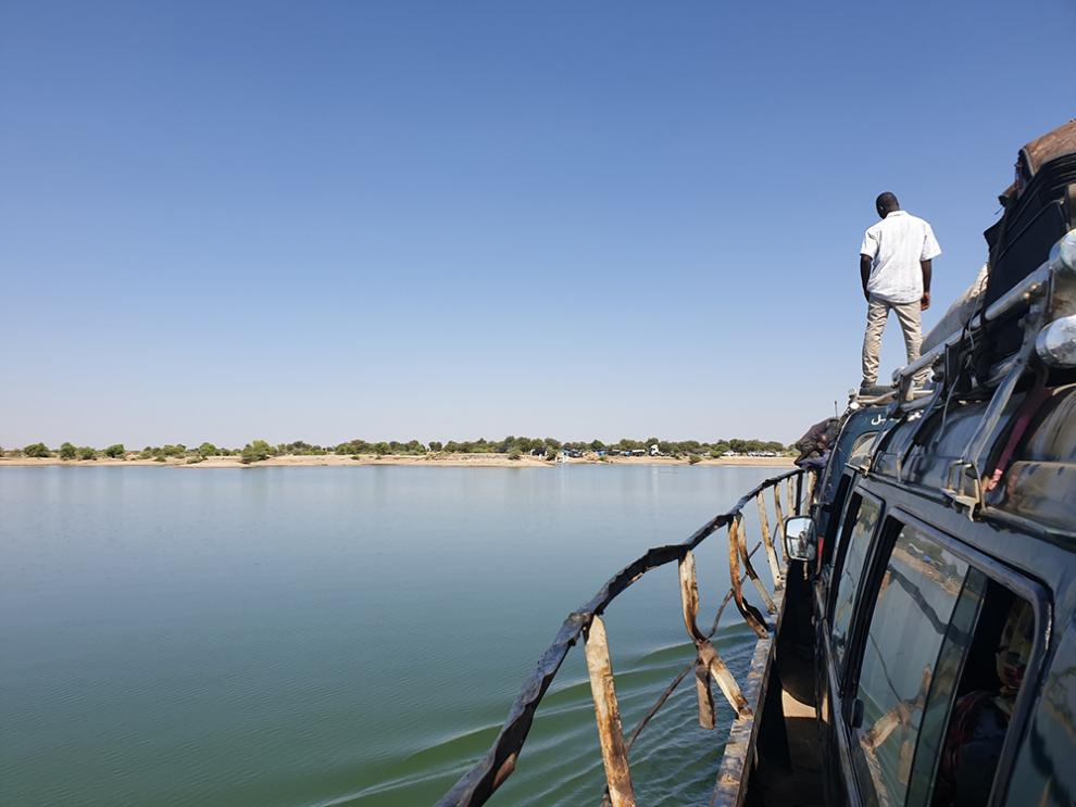 An man looks out on the deep green water during the ferry crossing.