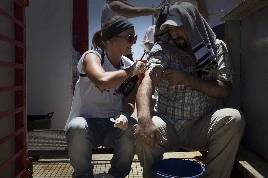A nurse gives a rescued man a check up on deck