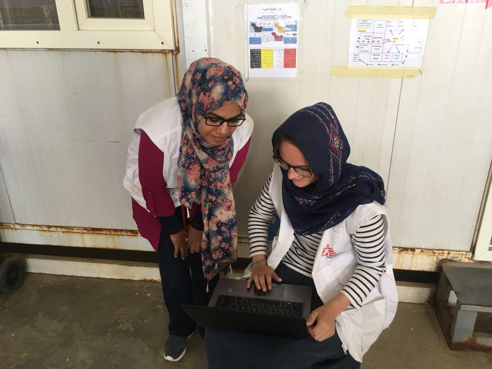An MSF epidemiologist and health promoter look at a laptop together
