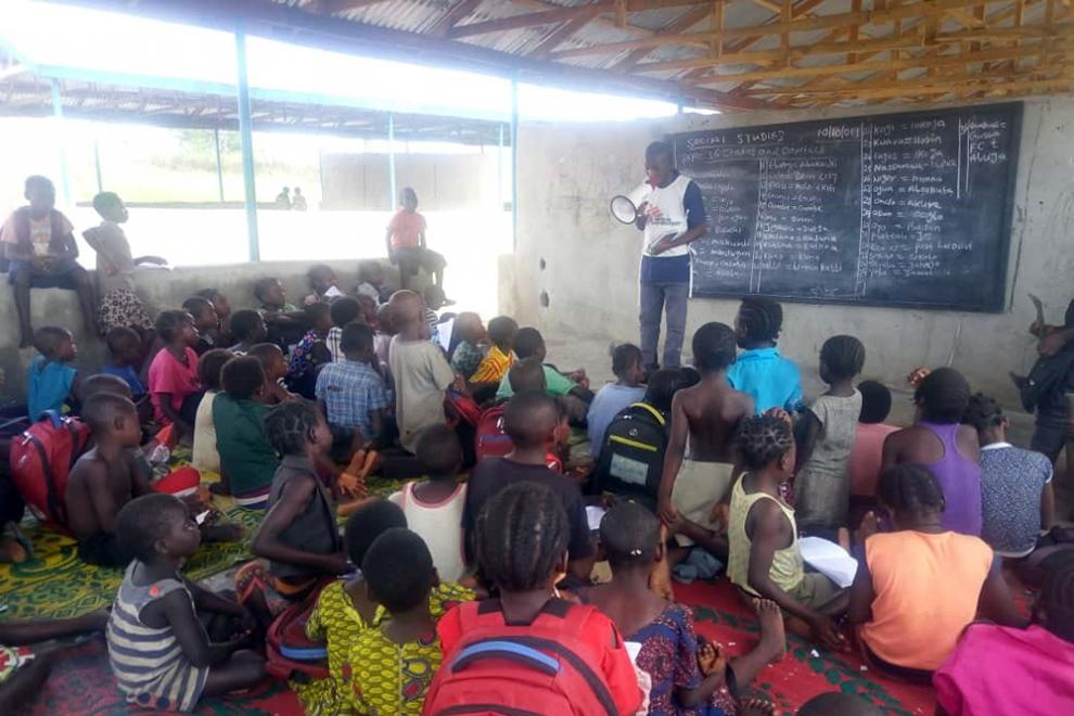 MSF health promoter supervisor John Asema presents to children in a camp for internally displaced people in Benue state
