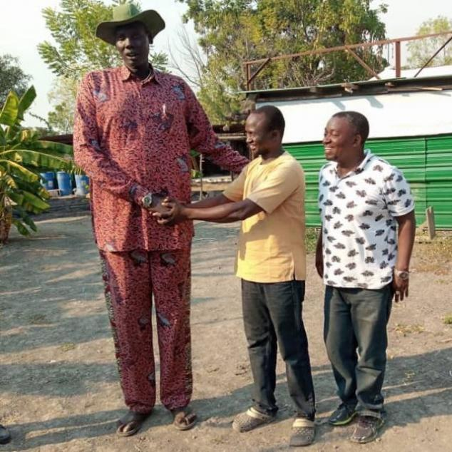 Mamman and a colleague meet a youth leader. He is nearly twice their height!
