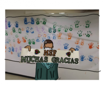 """A staff member holds a sign saying """"Thank you MSF"""" in front of the wall of footprints"""
