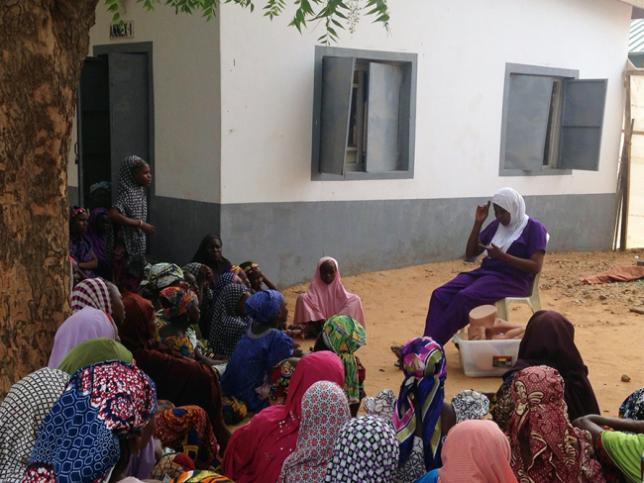 Women sit under a tree to listen to Bilkisu speak
