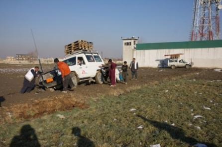 Camp volunteers and two MSF drivers work hard to free an MSF vehicle from the sticky mud at a camp in Kabul.