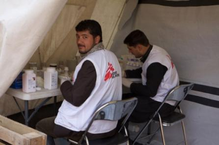 Satar, an MSF driver, assists the pharmacist in preparing prescriptions at a temporary clinic in Kabul.