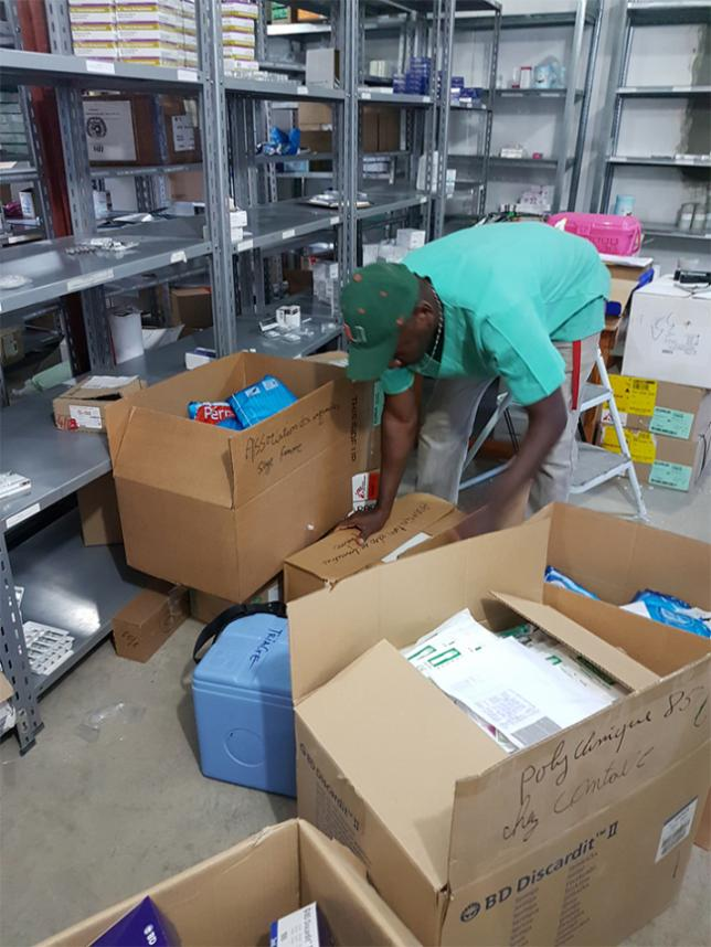 François, a pharmacy assistant, working hard sorting and boxing medication for donations