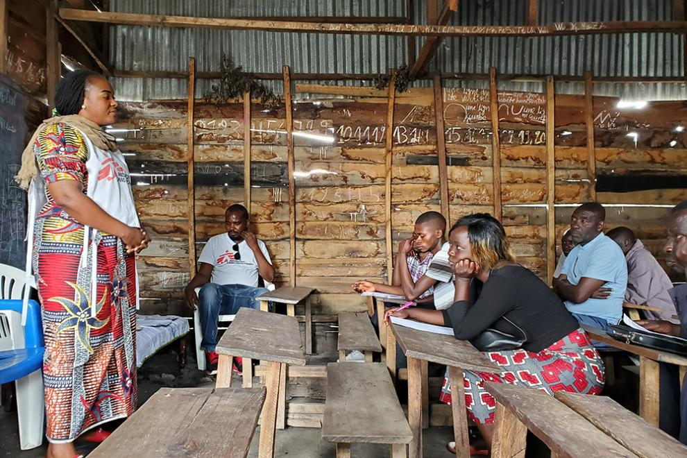 An MSF staff member hosts a COVID-19 health promotion training and information session with a group of volunteer community healthcare workers in the village of Kiziba, North Kivu province, DRC