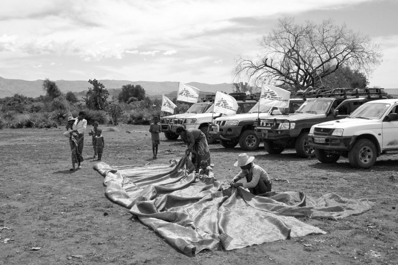 Women help build the shade nets for the clinic