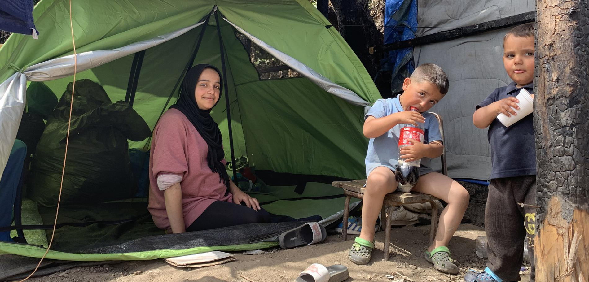 Shaza with her two sons in the summer tent where the family sleeps in Vathy camp, Samos