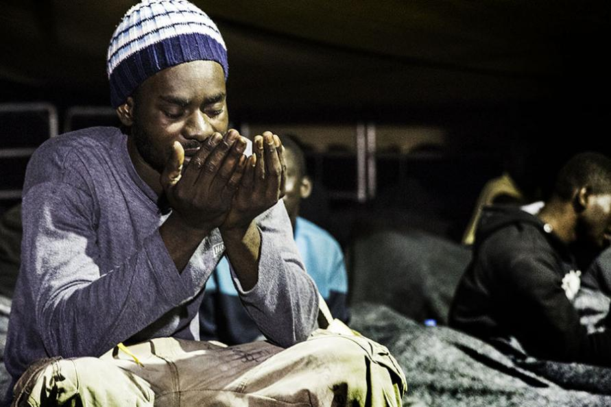 A rescued man prays on the deck of the ship